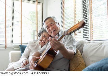 Happy Asian Senior Couple Enjoying Singing And Playing Acoustic Guitar Together On Sofa At Home. Joy