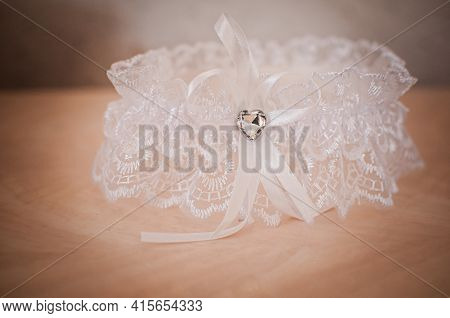 White Color Garter Lying On The Wooden Table