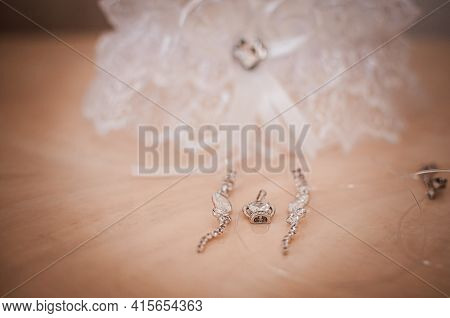 White Garter Earrings And Pendant Lying On The Wooden Table