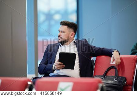 Young pensive businessman in formalwear using digital tablet and looking through window while sitting in lounge of modern airport
