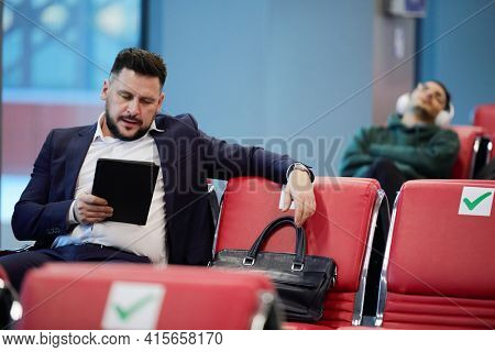 Young serious businessman in formalwear using digital tablet while sitting in lounge of modern airport against guy listening to music in headphones