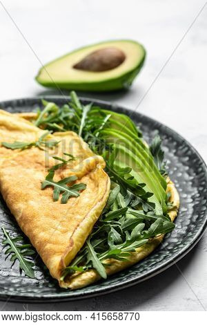 Stuffed Omelette With Avocado And Arugula On Light Background, Healthy Diet Food For Breakfast. Brea