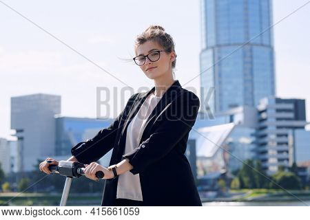 Young blond businesswoman in formalwear and eyeglasses standing on electric scooter against modern architecture on sunny day