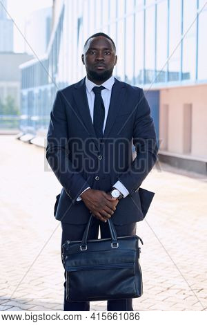 Young confident African businessman in formalwear standing in front of camera against exterior of modern building in urban environment