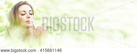 Beautiful young woman blowing dandelion lying on grass