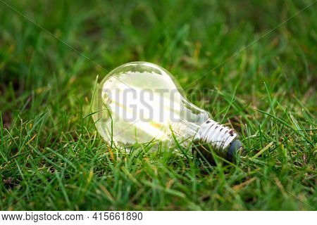 Energy Efficient Led Filament Lightbulb Glowing In Grass. Planet's Climat Change And Green Energy Co