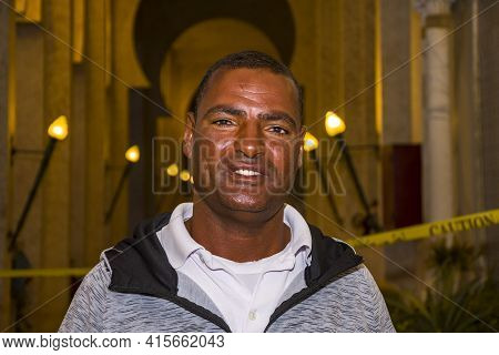 Portrait Of A Smiling Egyptian Man About 40 Years Old Against The Backdrop Of A City Landscape, His