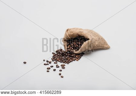 Hessian Sack Bag With Roasted Coffee Beans On White.