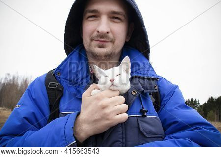 Man In Blue Jacket And Hood Holding White Kitten With Closed Eyes In His Bosom, Close-up.