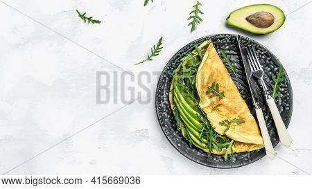 Frittata Omelette With Avocado And Arugula On Plate. Italian Omelet. Healthy Diet Food For Breakfast