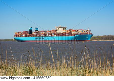 Stade, Germany - April 22, 2020: Container ship MORTEN MÆRSK on Elbe river heading to Hamburg. Beach and dune grass in foreground.
