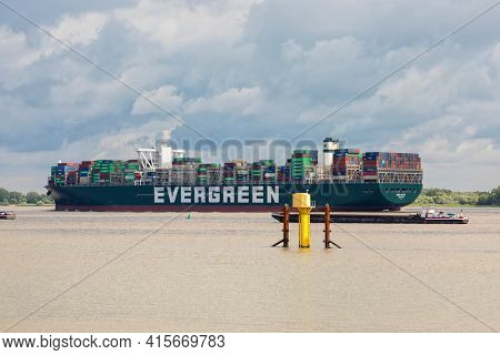 Stade, Germany - July 3, 2020: Container ship EVER GIFTED operated by EVERGREEN LINE and registered in Singapore leaving Hamburg on Elbe river
