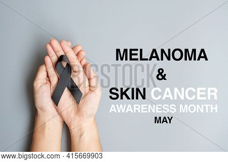 Melanoma And Skin Cancer, Vaccine Injury Awareness Month And Rest In Peace Concepts. Man Holding Bla