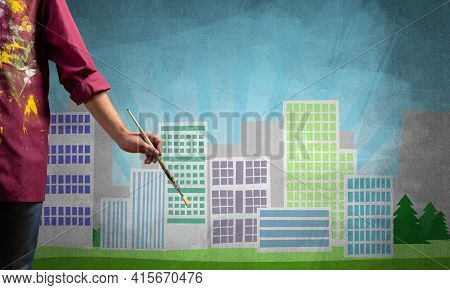 Close Up Artist Hand Holding Paintbrush. Painter In Shirt Standing On Background Colorful Picture Of
