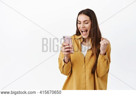 Image Of Girl Celebrating Win Online, Looking At Smartphone And Rejoicing, Winning Or Achieve Daily