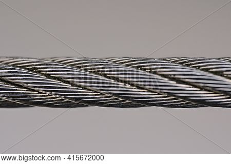 Beautiful Isolated Macro View Of Steel Wire Rope On Solid Gray Background. Metal Rope Fence, Edging