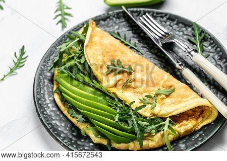Omelette With Avocado And Arugula On Plate. Italian Omelet. Healthy Breakfast Or Snack, Top View.