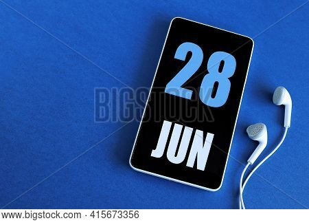 June 28. 28 St Day Of The Month, Calendar Date. Smartphone And White Headphones On A Blue Background