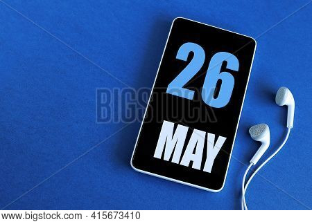 May 26. 26 St Day Of The Month, Calendar Date. Smartphone And White Headphones On A Blue Background.