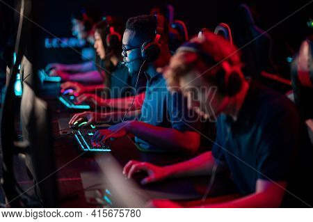 A Multi-racial Team Of Esports Athletes Conducts A Training Session Before An Online Shooter Tournam