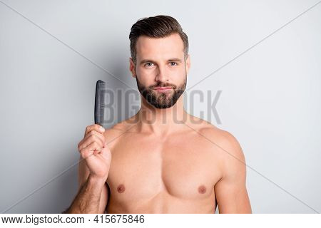 Photo Of Young Handsome Bristle Guy Hold Hairbrush Hairdo Balm Lotion Isolated Over Grey Color Backg
