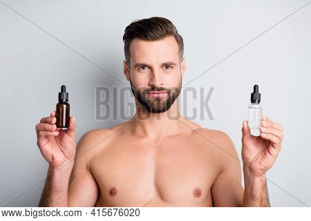 Photo Of Young Handsome Man Compare Two Liquids Oil Serum Facial Treatment Advert Isolated Over Grey