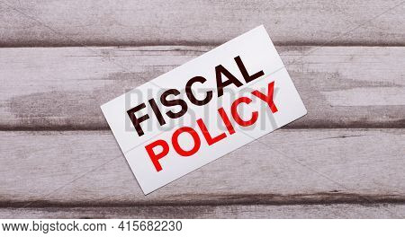 On A Wooden Background, There Is A White Card With Red Text Fiscal Policy