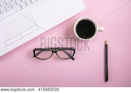 Flat Lay Workspace Table With White Laptop Computer, Cup Of Coffee And Eyeglasses, On Pink Backgroun