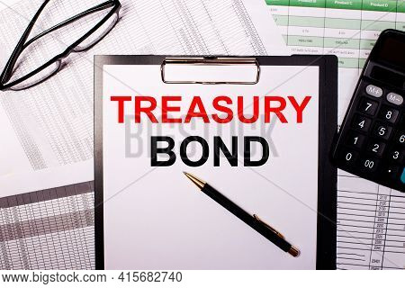 Treasury Bonds Is Written On A White Sheet Of Paper, Near The Glasses And The Calculator.