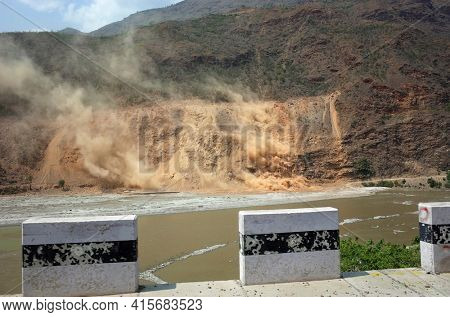 Himalayas, Nepal - June 12, 2019: New road construction in mountain, Wind blowing large dust clouds from landslides