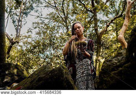 Caucasian Women With Dreadlocks With A Tibetan Bowl Among The Rocks