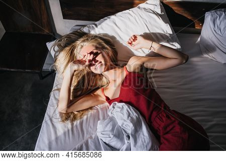 Happy Fair-haired Lady Hiding Face From Sunlight In Morning. Cheerful Female Model In Red Pajama Lyi