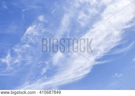 White Cirrus Rising Clouds Against Clear Blue Sky. Atmospheric Phenomenon. Natural Background. Copy