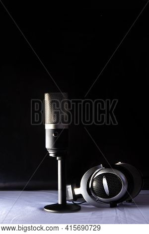 Professional Condenser Microphone And Headset On White Surface And Black Background, Low Key Portrai