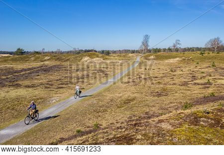 Diever, Netherlands - March 30, 2021: Active People Riding Their Bicycle In The National Park Drents