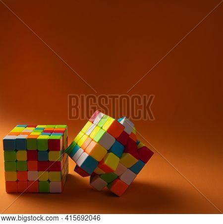 Araras, São Paulo, Brazil, April 4, 2021, Two Magic Cubes On Orange Background And Shadow, Selective