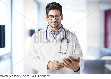 Shot Of Male Doctor Holding Digital Tablet In His Hand While Standing In Hospital's Foyer.