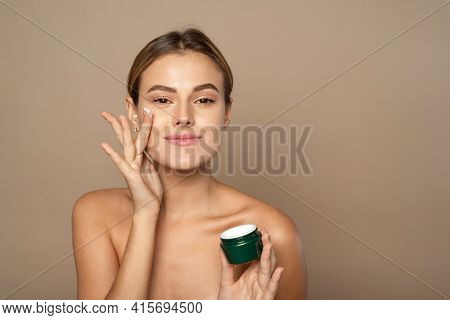Portrait Of A Pretty Young Smiling Woman With Clean Fresh Skin In The Studio On A Beige Background.
