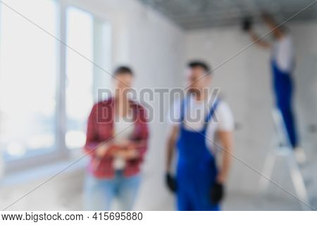 Blurred Background Of The Supervisor Checks The Work Of The Workers In The Apartment And Writes A No