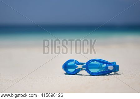 Blue Swimming Goggles Lie On The White Sea Sand On The Beach. Blue Swimming Gear On The Sand. The Co