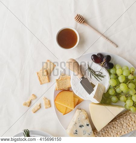 Cheese Plate Assortment Served With Honey, Grapes, Bread And Rosemary