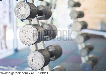 Rows Of Dumbbells In The Gym. Sports Equipment In The Gym. Empty Gym During Quarantine.