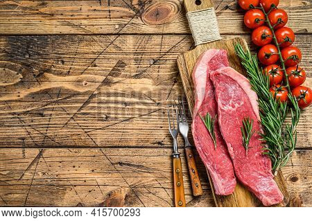Raw Top Sirloin Cap Or Picanha Steak On A Chopping Board. Wooden Background. Top View. Copy Space