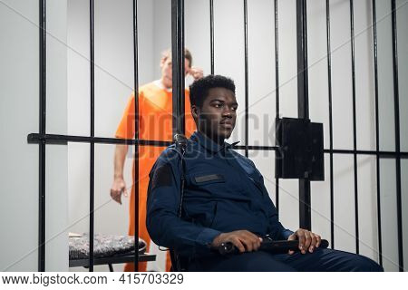 A Black Prison Guard Sits In Front Of Cages With Dangerous Criminals On A Chair With A Baton.