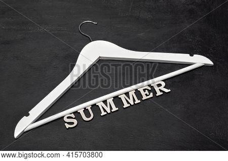 White Wooden Coat Hanger And Summer Inscription On Black Background. Summer Collection. Summer Sale