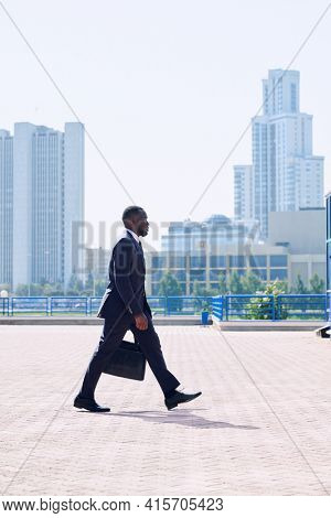 Young elegant African businessman in formalwear moving down sidewalk in front of camera against cityscape with skyscrapers and park