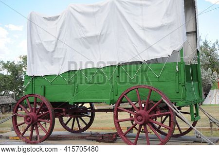 Covered Wagon From The Pioneer Days Displayed Outdoors.