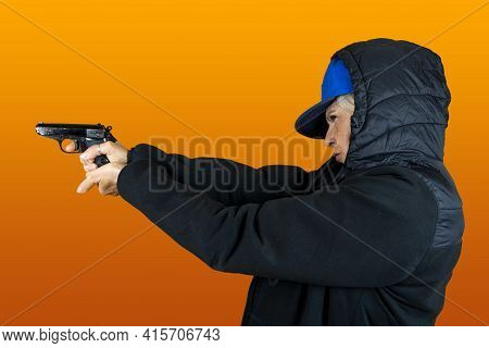 Funny Portrait Of Mature Woman. Lady Shoots The Gun Dressed As An Angry Rapper