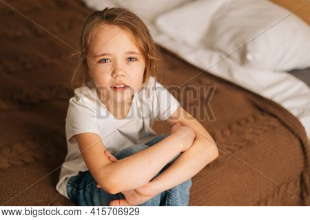 Top Close-up View Of Distraught Beautiful Little Girl With Wet Eyes From Tears Sits On Bed In Bedroo