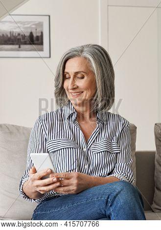 Happy Older Mature 50s Senior Woman Holding Smartphone Enjoying Using Mobile Apps Technology. Smilin